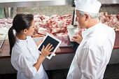 Side view of male and female butchers using digital tablet in store