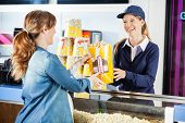 Happy female seller giving popcorn paperbag to pregnant woman at cinema concession stand