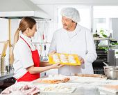 Happy male and female chefs discussing while holding pasta tray in commercial kitchen