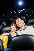 Happy loving mid adult couple watching film in movie theater