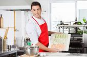 Portrait of confident male chef presenting raw ravioli pasta arranged on cutting board in commercial kitchen