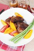 meat food : rare medium roast beef fillet with mango tomatoes and asparagus , served on white dish on red table map over wooden table