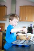 Young Boy Making Chocolate Cakes