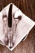 Old metal knife, spoon and fork on wooden background