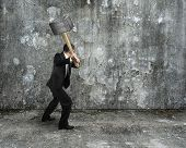 Businessman Hold Sledgehammer To Crack Old Mottled Concrete Wall