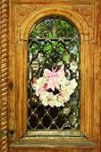 Beautiful wreath of flowers hanging on old wooden door