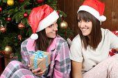 Beautiful girls twins in pajamas near Christmas tree at home
