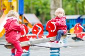 Two Little Sibling Kid Boys Playing Together On A Playground, Outdoors