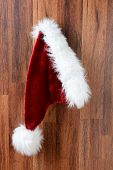 Closeup of a Santa Claus hat hanging from a nail on a rustic wooden wall.  Vertical Format.