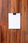 Blank sheets of paper held by a clip hanging from a nail in the middle of a dark wood wall. Vertical format. The blank white paper is ready for your copy.