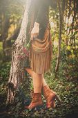 woman stand by the tree hold flowers in hand wearing leather handbag, green dress and brown ankle boots, retro colors