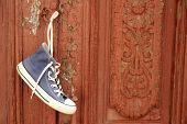 Sneaker hanging on wooden door