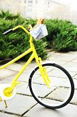 Beautiful yellow bicycle in park with tasty bread in basket