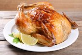 Delicious baked chicken on plate on table close-up