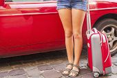 Abstract young girl near a car with a red suitcase.