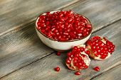 Juicy pomegranate seeds, on old wooden table