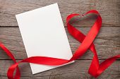 Valentines day heart shaped red ribbon and blank greeting card over wooden table background