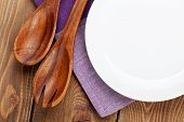 Wood kitchen utensils and empty plate over wooden table background with copy space