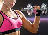 fitness, healthcare and dieting concept - close up of young sporty woman with heavy steel dumbbell