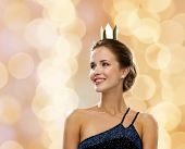 people, holidays, royalty and glamour concept - smiling woman in evening dress wearing golden crown over beige lights background