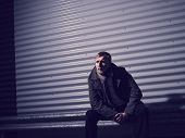 stock photo of overcoats  - Fashionable young man wearing a warm overcoat corrugated iron wall on background  - JPG