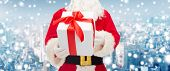 christmas, holidays and people concept - close up of santa claus with gift box over snowy city background