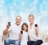 holidays, technology, advertisement and people concept - smiling family with smartphones over blue lights background