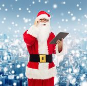 christmas, holidays, technology and people concept - man in costume of santa claus with tablet pc computer over snowy city background