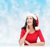 christmas, winter, holidays, happiness and people concept - smiling woman in santa helper hat over blue lights background