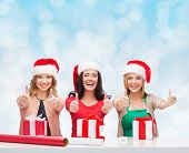 christmas, holidays, decoration, gesture and people concept - smiling women in santa helper hats with decorating paper and gift boxes showing thumbs up over blue lights background