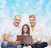 family, childhood, holidays, technology and people concept - smiling family with laptop computer over blue lights background