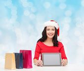 christmas, technology and people concept - smiling woman in santa helper hat with shopping bags and tablet pc computer over blue lights background