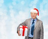 business, christmas, presents and people concept - smiling senior man in suit and santa helper hat with gift over blue lights background