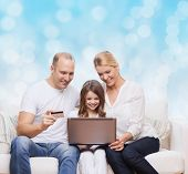 family, holidays, shopping, technology and people concept - happy family with laptop computer and credit card over blue lights background