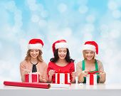 christmas, holidays, celebration, decoration and people concept - smiling women in santa helper hats with decorating paper and gift boxes over blue lights background
