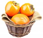 Ripe persimmons in wicker basket isolated on white