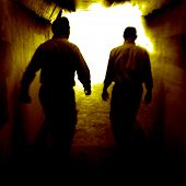 Two people walking through a tunnel towards the light