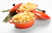 Pasta baked with shrimps and cheese in ceramic pot, isolated on white