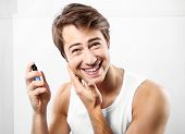image of shaving  - Young handsome man after shave balm is applied on the skin face - JPG