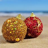 closeup of some ornamented christmas balls on the sand of a beach, with the sea and the horizon at the background