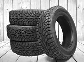 Stack of four new black tyres for winter car on wooden floor in vintage room with wall background