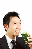 Japanese businessman drinks green vegetable juice