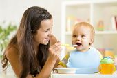 Beautiful young woman feeds her son baby