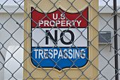 stock photo of chain link fence  - Sign behind chain link fence warns against trespassing - JPG