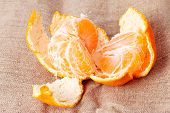 Disassembled tangerine close-up on sacking