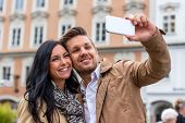 a young couple making a self portrait with a cell phone. selfies are in.