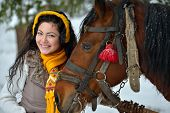 beautiful brunette woman portrait with horse in winter