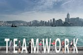Concept of teamwork with group of business people stand with 3d text.