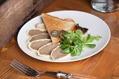 pate sliced on a plate with toast white bread