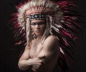 picture of headdress  - Naked indian strong man posing with traditional native american make up and headdress looking at the camera - JPG